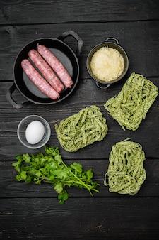 Ensemble d'ingrédients à la carbonara de saucisse de pâtes non cuites, sur fond de table en bois noir, vue de dessus à plat