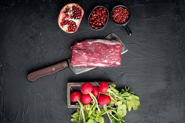 Ensemble d'ingrédients carpaccio crus, sur table en pierre noire, vue de dessus à plat