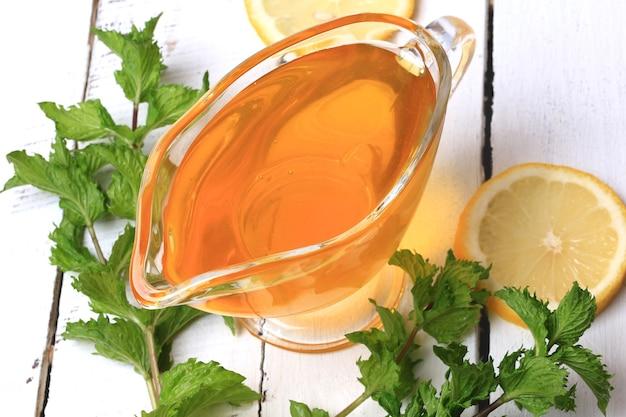 Ensemble d'ingrédients de citron menthe miel pour limonade maison sur un fond en bois blanc