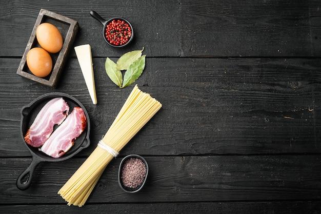 Ensemble d'ingrédients de pâtes carbonara, sur table en bois noir, vue de dessus à plat, avec copie espace