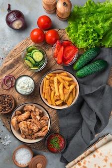 Un ensemble d'ingrédients pour faire du shawarma, des tacos sur un mur gris. ou un déjeuner complet avec frites, viande et légumes frais. vue de dessus, verticale. fast food.