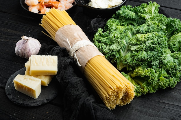 Ensemble d'ingrédients spaghetti vert, sur table en bois noir