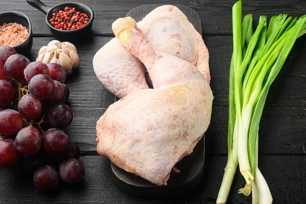 Ensemble d'ingrédients surprise au poulet sucré, avec raisin et persil, sur une planche à découper en bois, sur une table en bois noire