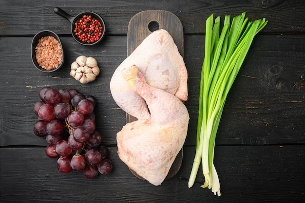 Ensemble d'ingrédients surprise de poulet sucré, avec du raisin et du persil, sur une planche à découper en bois, sur une table en bois noir, vue de dessus à plat
