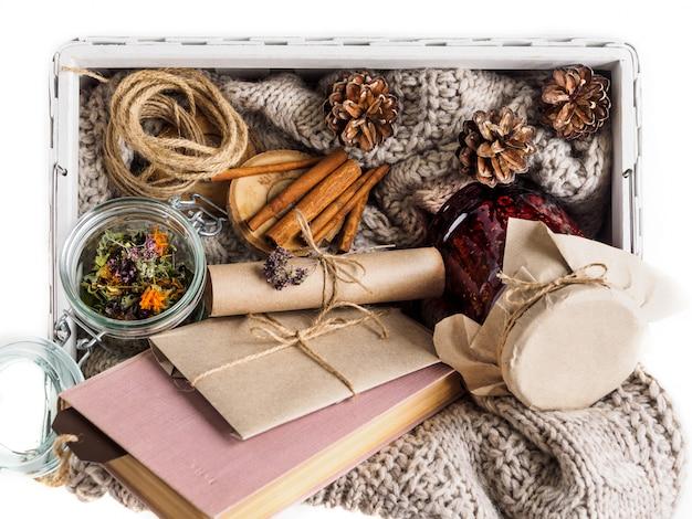 Un ensemble d'ingrédients utiles pour un traitement à la maison. confiture et herbes sèches pour infuser du thé. livre et enveloppe. ambiance feutrée en hiver et en automne