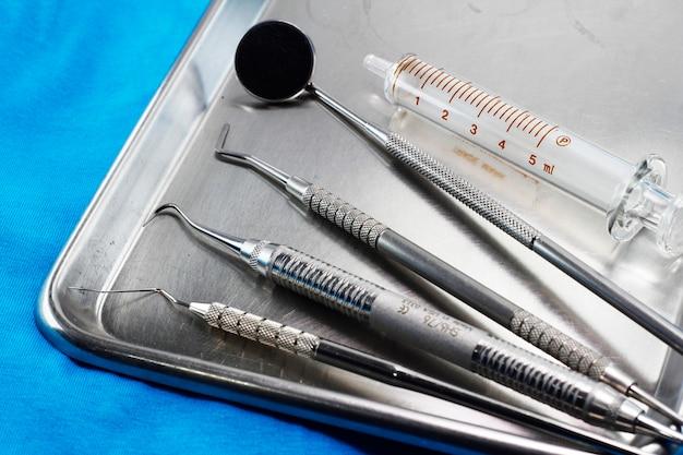 Ensemble d'instruments dentaires dans un plateau en acier inoxydable