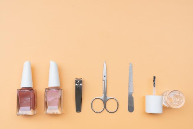 Ensemble d'instruments et d'outils de manucure avec vernis à ongles, vue de dessus, espace copie