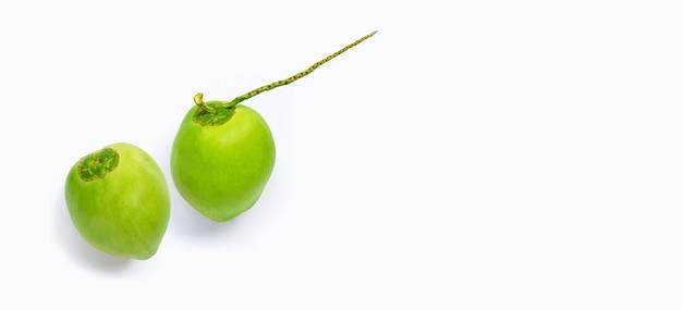 Ensemble de jeunes fruits de noix de coco verts frais sur une surface blanche