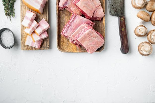 Ensemble kalbi de côtes de boeuf cru, avec ingrédients, et vieux couteau de couperet de boucher, sur fond de pierre blanche, vue de dessus à plat, avec espace de copie pour le texte