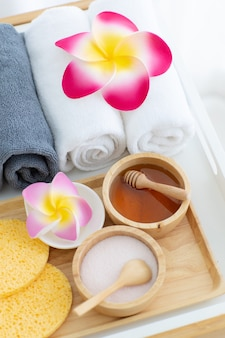 Ensemble de latte de traitement spa et de miel dans un bol en bois avec des rouleaux de serviettes propres avec fleur de frangipanier colorée.