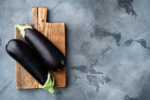 Ensemble de légumes aubergine aubergine violet réfléchissant vibrant, sur fond de pierre grise, vue de dessus à plat, avec espace de copie pour le texte