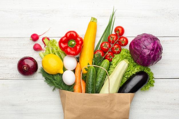 Ensemble de légumes et d'herbes dans un sac en papier sur un fond en bois blanc vue de dessus