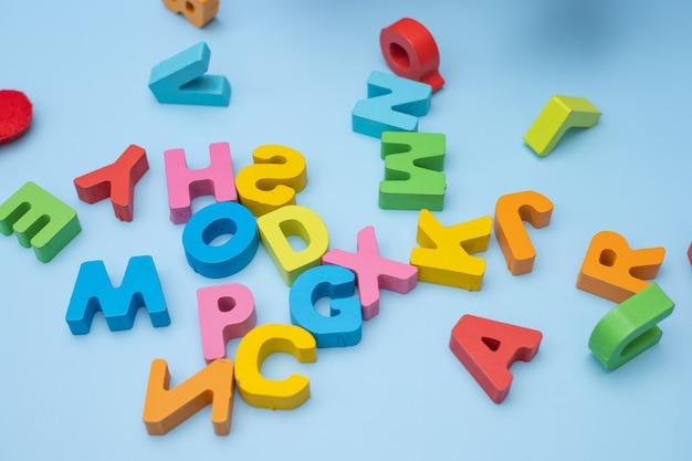 Ensemble de lettres en bois colorées sur fond bleu. vue de dessus.
