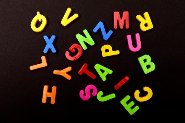 Ensemble de lettres en plastique colorées sur fond noir