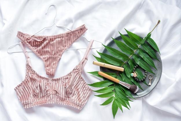 Ensemble de lingerie en dentelle sexy glamour élégant allongé sur le lit avec des feuilles vertes