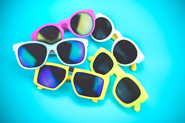 Ensemble de lunettes de soleil gisait sur le sol bleu, concept d'été