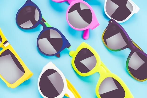 Ensemble de lunettes de soleil s'étendent sur le sol bleu