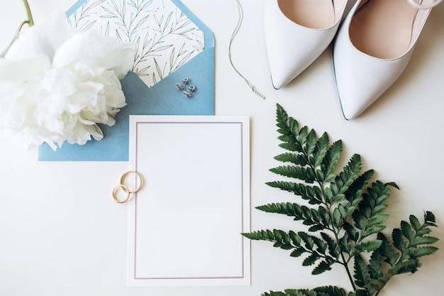 Ensemble de luxe d'invitations de mariage, anneaux de mariage, accessoires élégants de la mariée sur fond blanc.