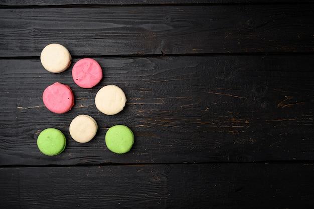 Ensemble de macarons français colorés, sur fond de table en bois noir, vue de dessus à plat, avec espace de copie pour le texte