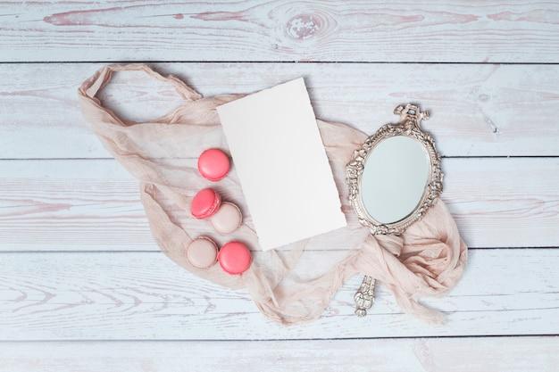 Ensemble de macarons près de papier et miroir entre textile