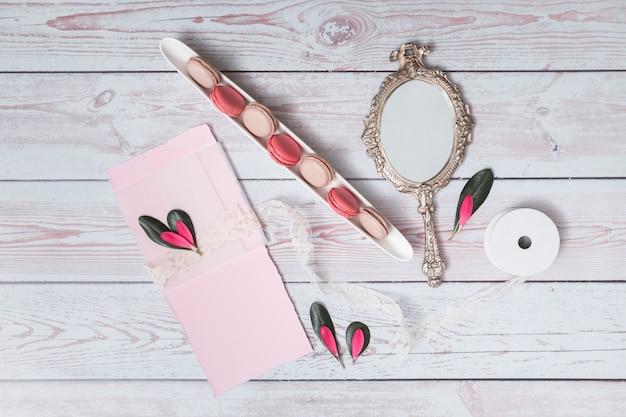 Ensemble de macarons près de papier, de pétales et de miroir