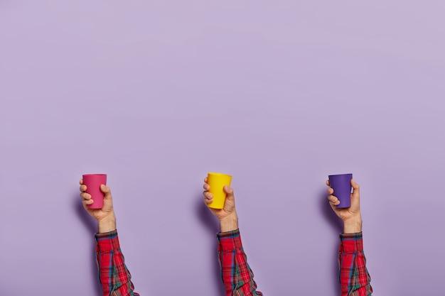 Ensemble de mains mâles avec des gobelets en plastique vides colorés