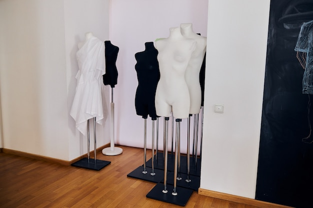 Ensemble de mannequins féminins se dresse dans un mur blanc aumbry près du tableau noir dans un studio de design de mode léger