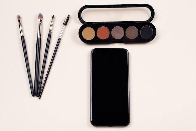 Ensemble de maquillage et cosmétiques décoratifs près de téléphone mobile à écran noir vide sur la scène beige