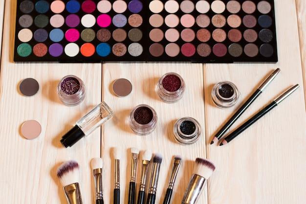 Ensemble de maquillage de cosmétiques professionnels décoratifs sur bois clair.