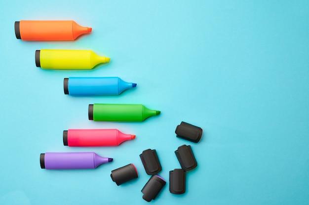 Ensemble de marqueurs permanents colorés ouverts sur le mur bleu. fournitures de bureau, accessoires scolaires ou éducatifs, outils d'écriture et de dessin