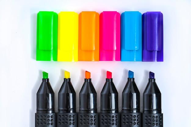 Ensemble de marqueurs surligneurs triés par couleur alignés et découverts sur fond blanc. premier plan.