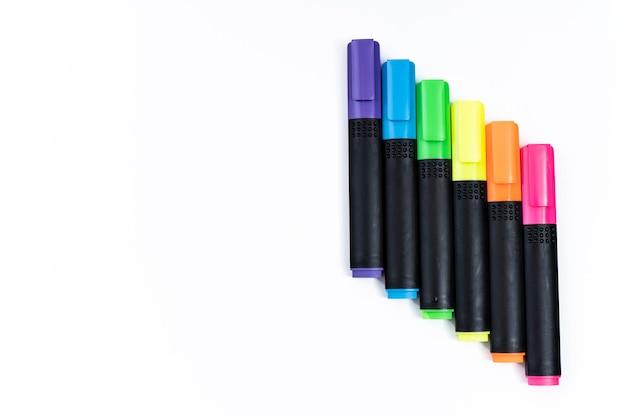 Ensemble de marqueurs surligneurs triés par couleur alignés en échelle sur fond blanc. espace de copie.