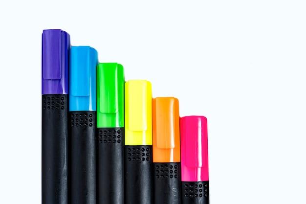 Ensemble de marqueurs surligneurs triés par couleur alignés en échelle sur fond blanc. premier plan.