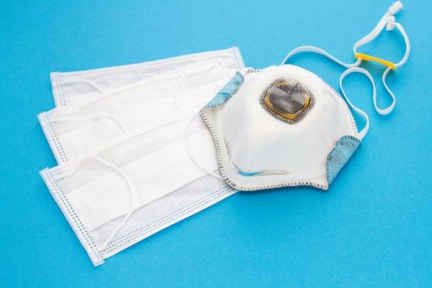 Ensemble de masques médicaux et un respirateur pour la protection individuelle sur fond bleu. concept épidémique