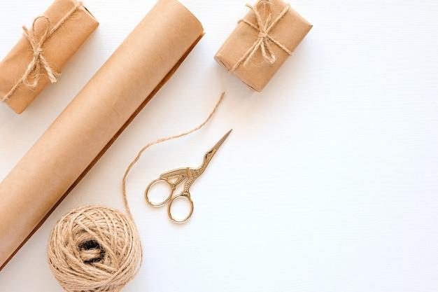 Ensemble de matériaux pour emballer les cadeaux de vacances. papier kraft, ficelle de jute, ciseaux, boîtes sur fond blanc