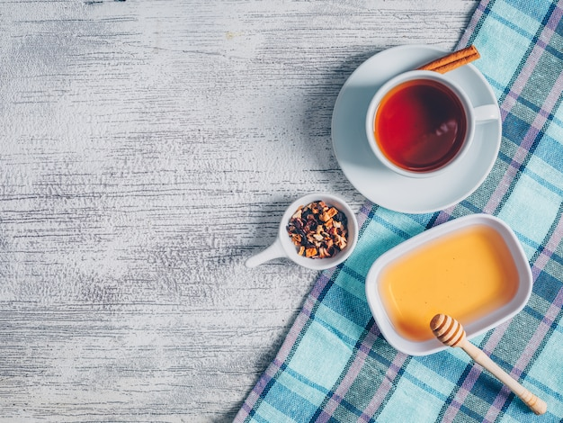 Ensemble de miel et d'herbes à thé et une tasse de thé sur un tissu de pique-nique et un fond en bois gris. vue de dessus. espace pour le texte