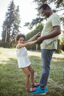 Ensemble. mignon enfant bouclé assis jouant avec son père et se sentant heureux