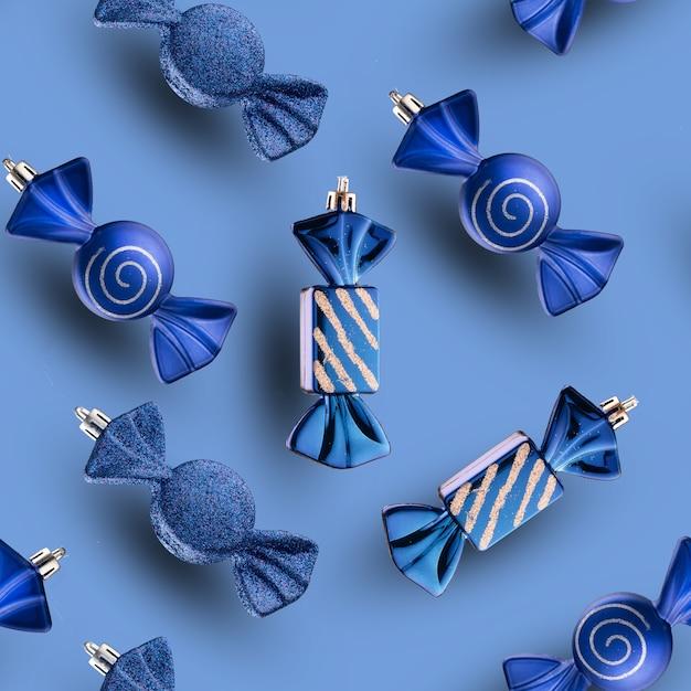 Ensemble de modèle sans couture de jouets de noël, bonbons sucrés bleus sur un mur bleu clair.