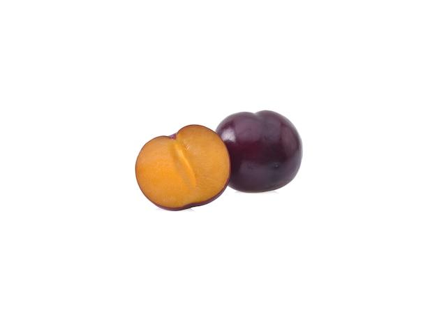 Ensemble et moitié de prunes cerises rouges isolés sur fond blanc