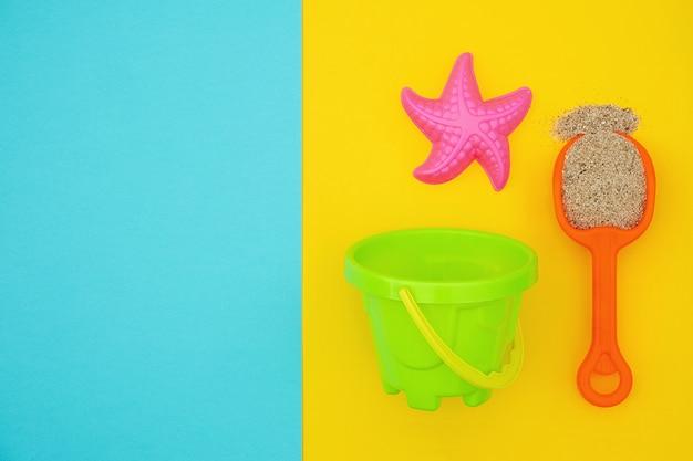 Ensemble multicolore de jouets pour enfants pour jeux d'été dans un bac à sable ou sur une plage de sable fin sur fond bleu et jaune