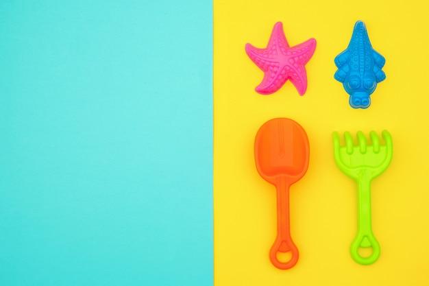 Ensemble multicolore de jouets pour enfants pour les jeux d'été dans un bac à sable ou sur une plage de sable fin sur fond jaune et bleu avec espace de copie