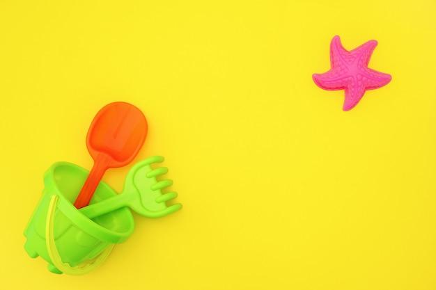 Ensemble multicolore de jouets pour enfants pour jeux d'été dans un bac à sable ou sur une plage de sable fin sur fond jaune