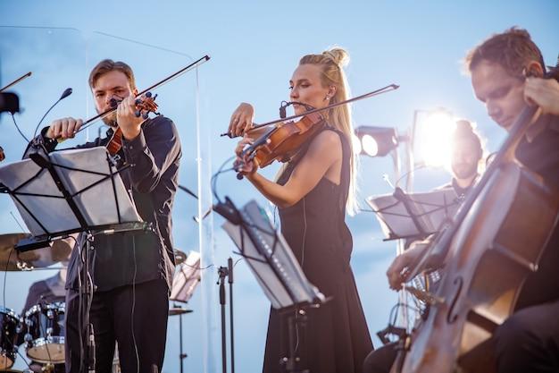 Ensemble musical jouant de la musique instrumentale classique contre le ciel bleu