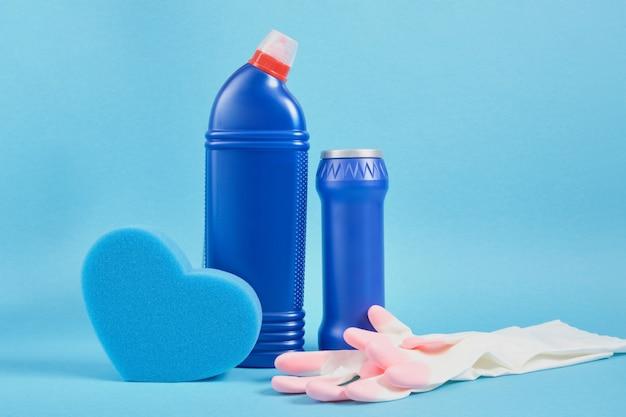 Ensemble de nettoyage coloré pour différentes surfaces dans la cuisine, la salle de bain service de nettoyage et concept de nettoyage de printemps. copie espace fond bleu éponge, gants et bouteilles de détergent