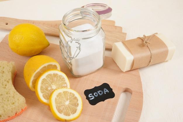Ensemble de nettoyage écologique, soda et citron pour le nettoyage, concept de mode de vie zéro déchet. bicarbonate de soude dans un bocal en verre, savon, luffa et citron tranché sur fond beige