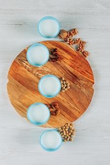 Ensemble de noisettes, amandes et plusieurs noix et tasses de lait sur un fond de planche à découper en bois et en bois blanc. vue de dessus.