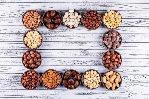 Ensemble de noix de pécan, pistaches, amandes, arachides, et assortiment de noix et fruits secs dans un mini bols différents en forme de rectangle sur une table en bois blanc