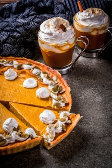 Ensemble de nourriture traditionnelle d'automne. halloween, thanksgiving. latte épicé à la citrouille, tarte à la citrouille et tartalets avec crème fouettée et graines de citrouille, soupe à la citrouille, sur une table en pierre noire. fond