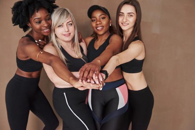Ensemble, nous pouvons tout faire. groupe de femmes multiethniques debout contre l'espace brun
