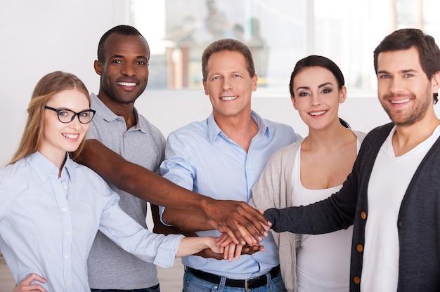Ensemble, nous sommes plus forts ! groupe de gens d'affaires joyeux en tenue décontractée se tenant près les uns des autres et se tenant la main